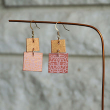 Load image into Gallery viewer, Two-tiered square dangle earrings made from recycled chipboard, hand painted in light pink and pink gold, and made with gold ear wire.