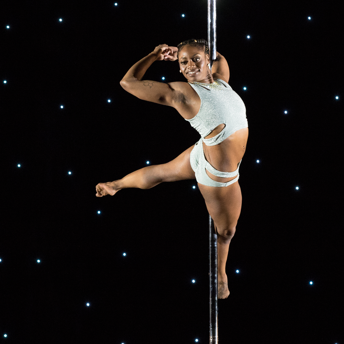 Candi Marie is in a twisted upright pose on a pole