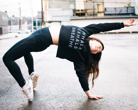 Evie wearing an Exhale Movement cropped hoodie while in backbend