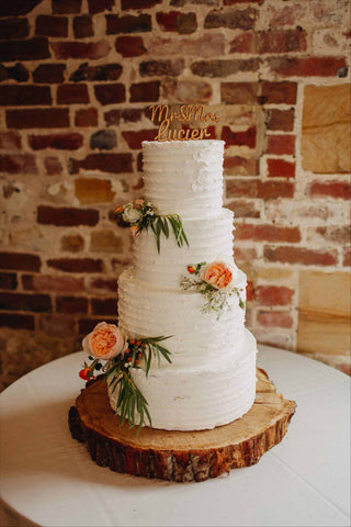 Buttercream covered wedding cake with fresh flowers