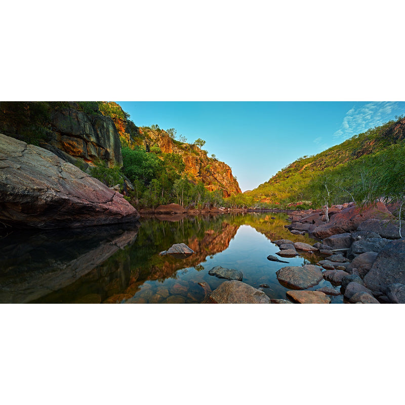 Sunrise reflects the gorge back into still waters of Koolpin Gorge, Kakadu National Park.