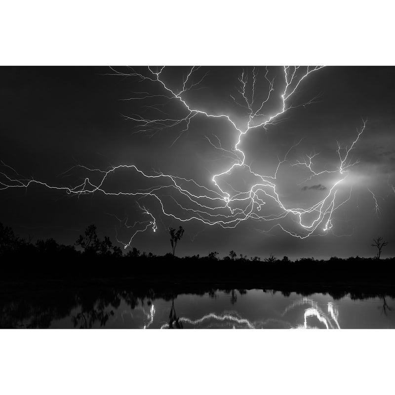 Black night time skies lit up by crawler lighting running across the sky over a dam on a cattle station.