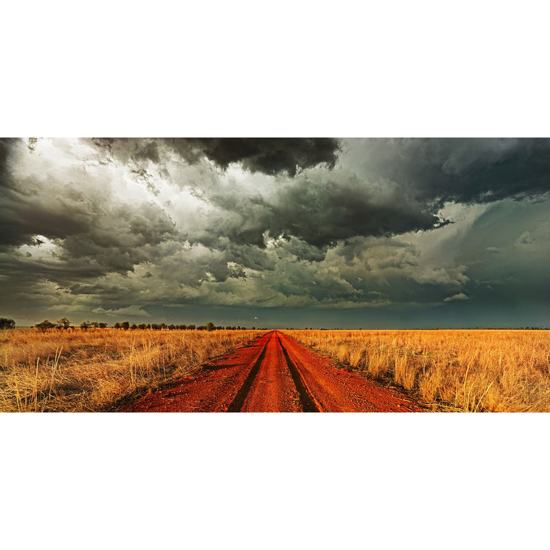 Grey stormy clouds over a red dirt track with deep wheel ruts with golden grass on the sides from the last light of the day.