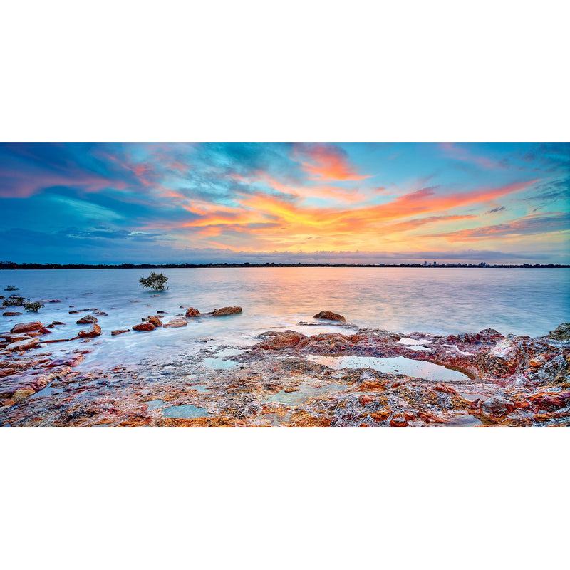 Red sunset over the rocks pf Nightcliff foreshore.