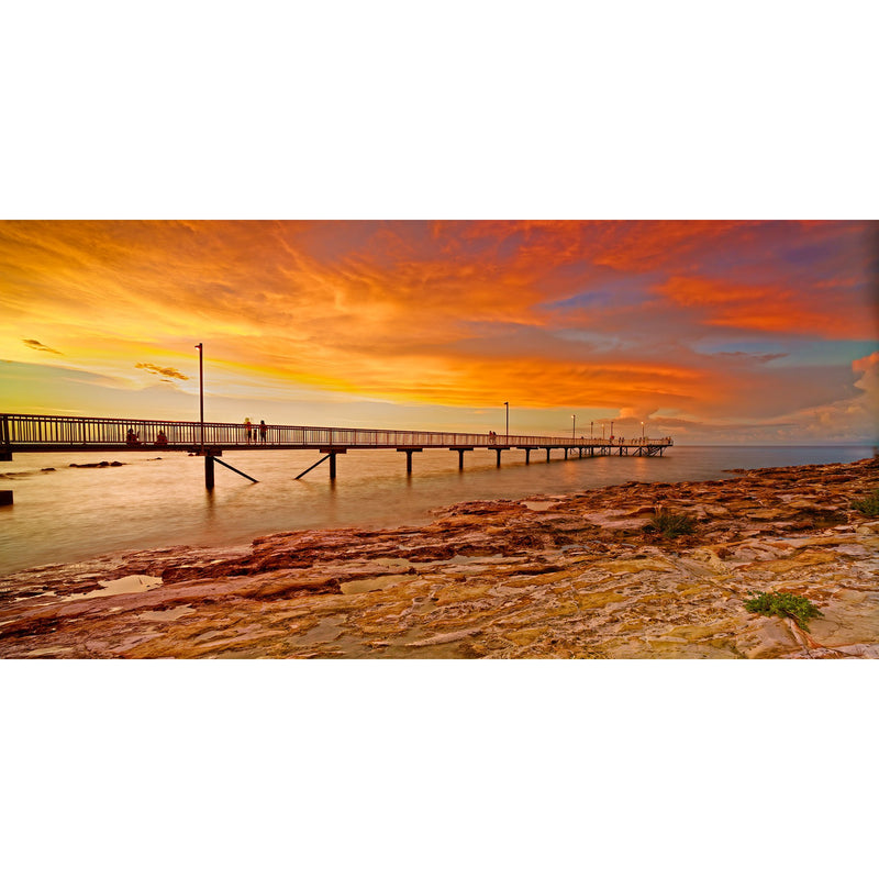 A bright orange sunset reflects onto the clouds above Nightcliff Jetty, Darwin while a King tide is on the rise.