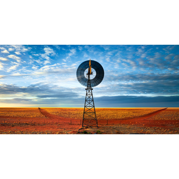 A windmill stands on a turkey nest water point under blue skies with station tracks disappearing to the horizon line.