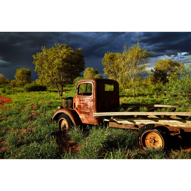 The rusted body of a trucked wrecked at a cattle stations entrance stands guard under stormy desert skies.