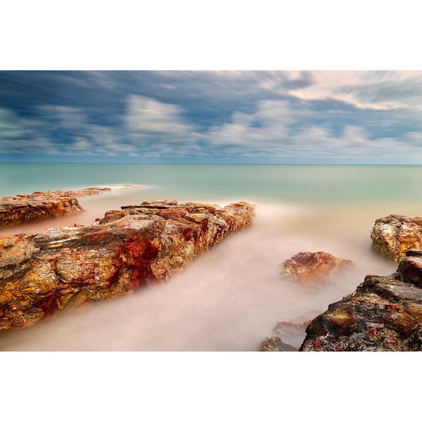 Striking rock formations of Nightcliff reach out into green waters