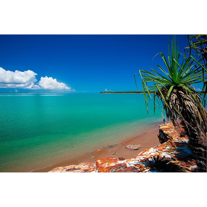 The bright blue waters gently lap the shores of Fannie Bay as pandanus lined cliffs overlook.