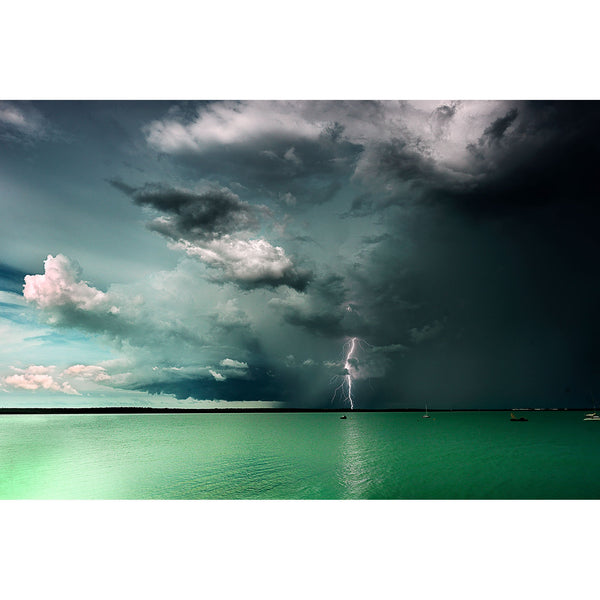 Green waters under a towering storm cell as lighting strikes in the distance in Darwin Harbour.