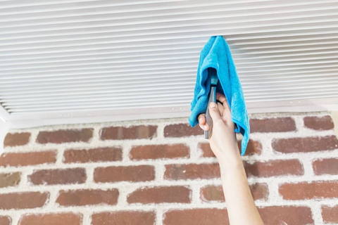 Cleaning an Air Vent on the Ceiling