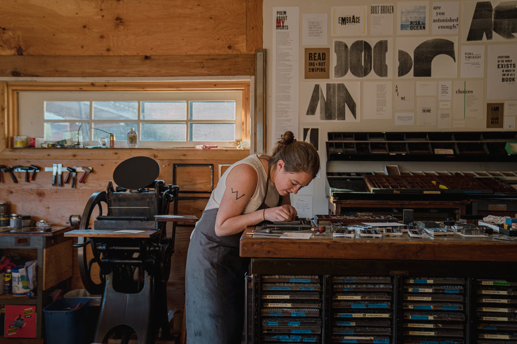 Golding Jobber press, Myrna working on type, prints on the wall at Expedition Press