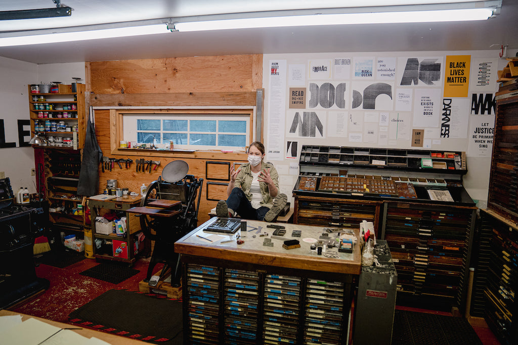 Myrna talking intently in the middle of her shop, Expedition Press