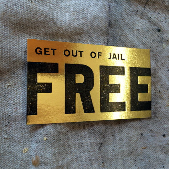 """""""get out of jail free"""" printed on gold foil card"""