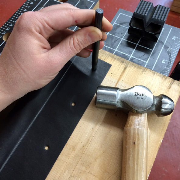 punching holes in a leather book spine for rivets
