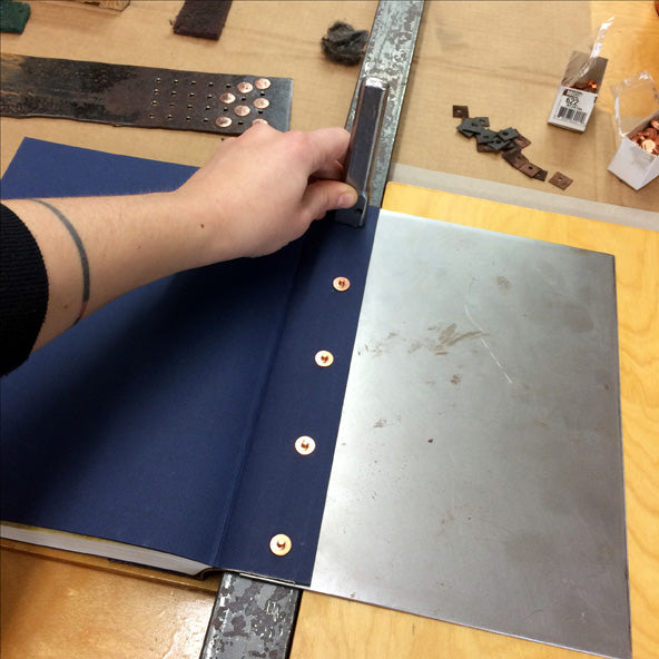 setting copper rivets in a leather book spine to attach cover