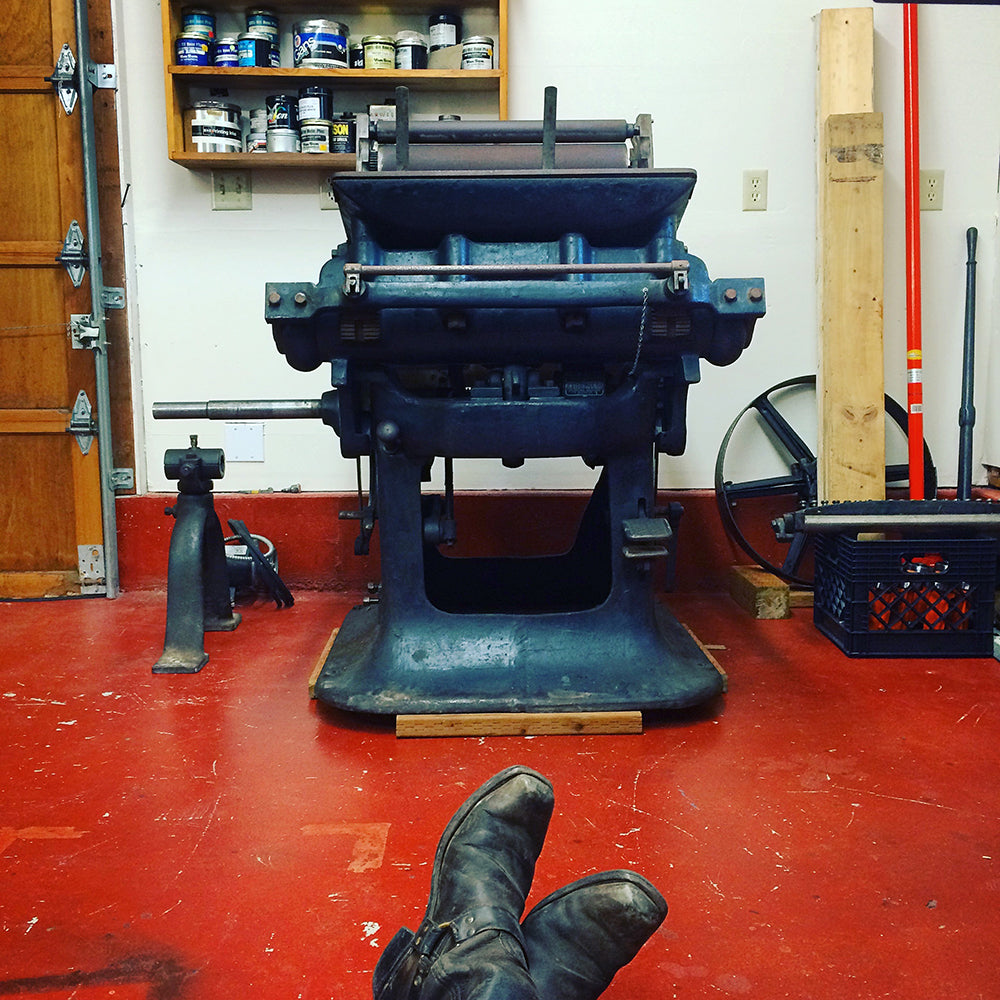 Colt's Armory printing press with boots in foreground