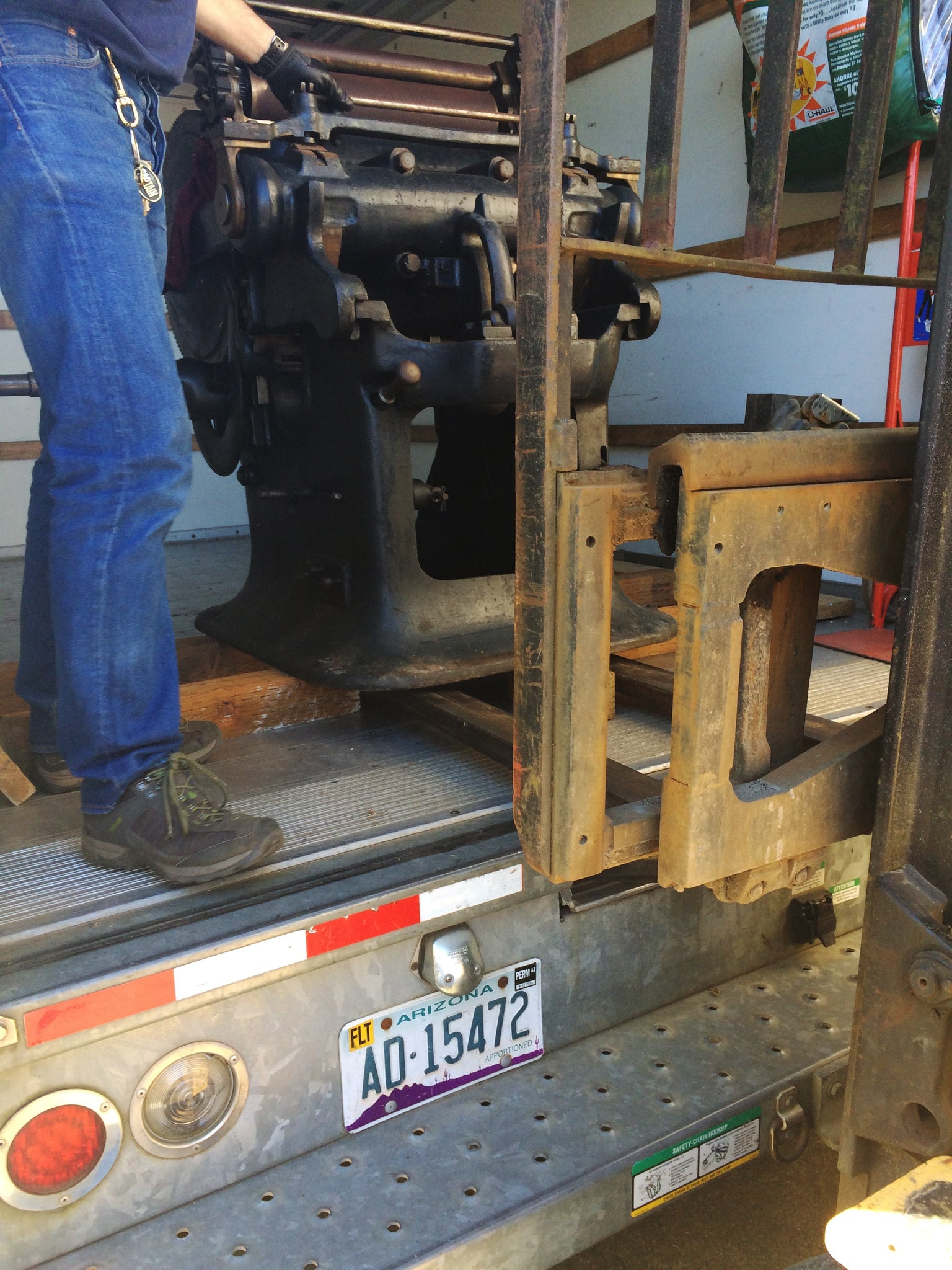 printing press at edge of back of truck with forklift