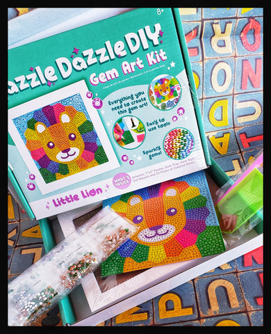 Razzle Dazzle Gem Art Kit 1 Artwork (5.9 in x 5.9 in, 15cm x 15cm)  1 Wooden Frame (7 in x 7 in, 17.8cm x 17.8cm)  1 Gem Tray   1 Gem Stylus   1 Gem Square  22 Packs of Colored Gems  ADA The Gilded Page Santa Fe