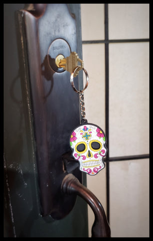 White rubberized sugar skull key ring. 2.5 x 5 inches in package. ADA The Gilded Page Santa Fe