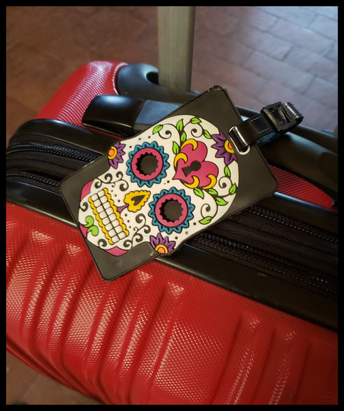 White rubberized sugar skull luggage tag . 3.5 x 6 inches in package. ID badge on flip side ADA The Gilded Page Santa Fe