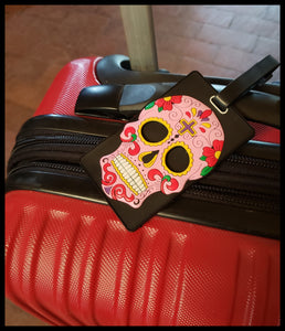 Pink  rubberized sugar skull luggage tag . 3.5 x 6 inches in package. ID badge on flip side ADA The Gilded Page Santa Fe