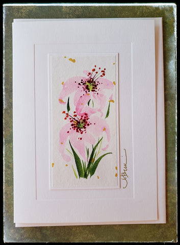 "May Lily Flower Hand Painted Card The exotic stargazer lily with its heavenly scent symbolizes innocence and purity of the heart and majesty.  Gold accents  Individually hand-painted on rice paper  Hand-painted images will vary  BLANK INSIDE  5.5"" x 7.5"" with envelope ADA The Gilded Page Santa Fe"