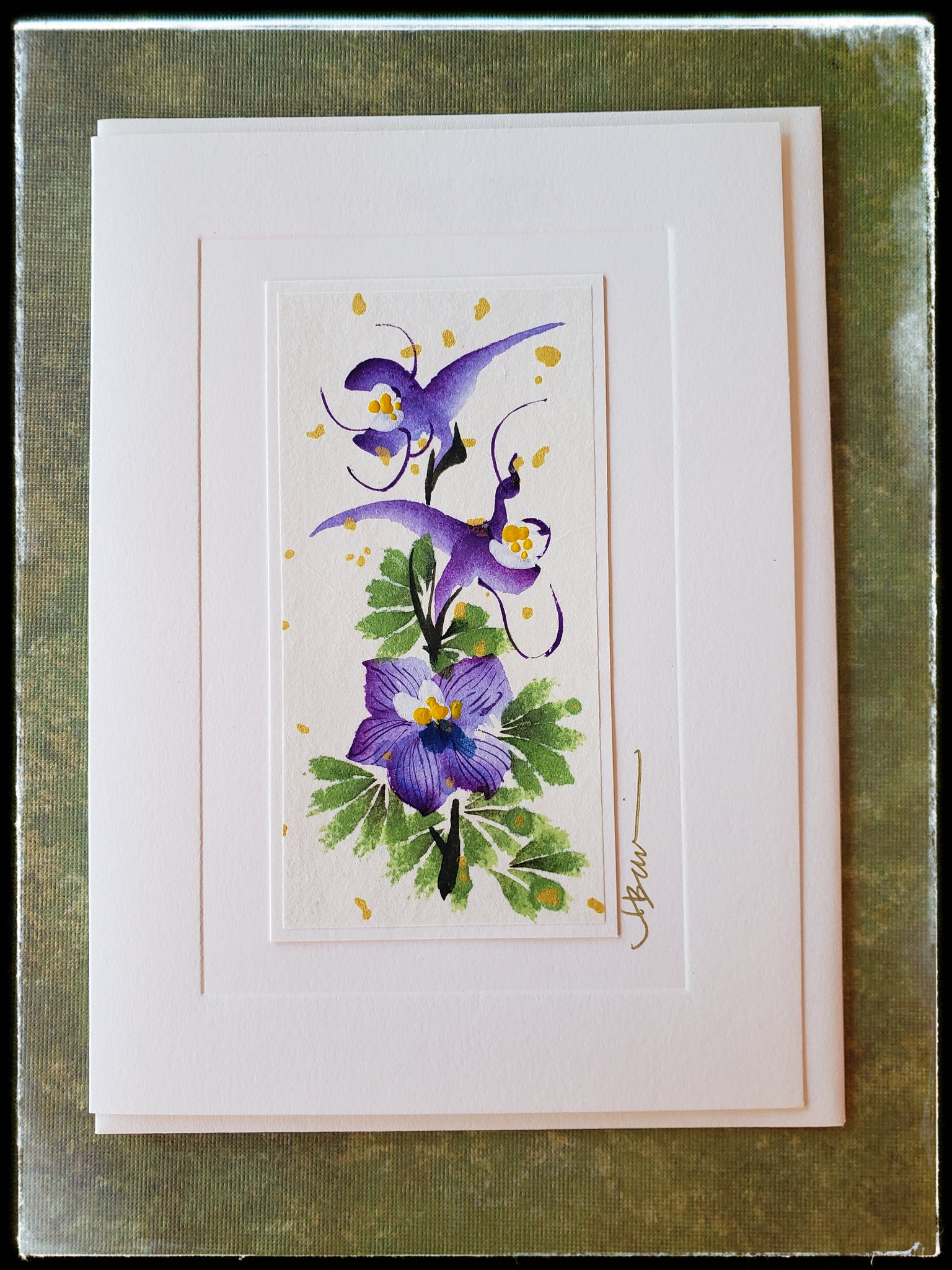 "July Larkspur Flower Hand Painted Card Lively and spirited, the Larkspur symbolizes laughter, and open heart and ardent attachment.   Gold accents  Individually hand-painted on rice paper  Hand-painted images will vary  BLANK INSIDE  5.5"" x 7.5"" with envelope ADA The Gilded Page Santa Fe"