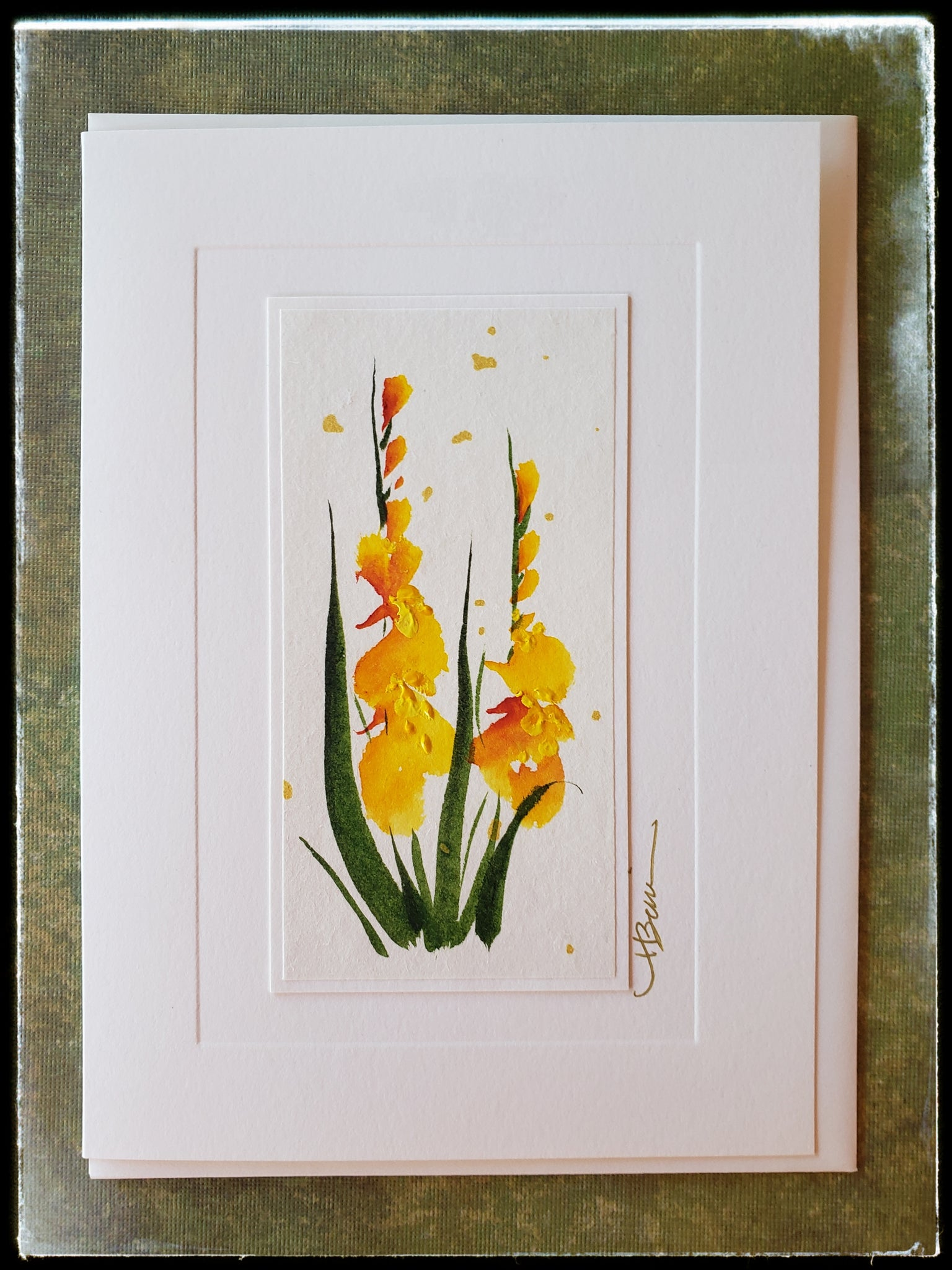 "August Gladiolus Flower Hand Painted Card Sleek and elegant, Gladiolus symbolizes grace, strength of character and moral integrity.  Gold accents  Individually hand-painted on rice paper  Hand-painted images will vary  BLANK INSIDE  5.5"" x 7.5"" with envelope ADA The Gilded Page Santa Fe"