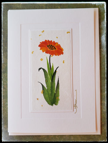 "October Calendula Flower Hand Painted Card Part of the Marigold family, calendula was the most sacred flower of ancient India. The flower blossom follows the path of the sun through the day. It symbolizes admiration and an abundance of joy.   Gold accents  Individually hand-painted on rice paper  Hand-painted images will vary  BLANK INSIDE  5.5"" x 7.5"" with envelope ADA The Gilded Page Santa Fe"
