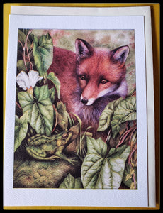 "A fox with a frog in some bushes. Fox and frog are starring at each other. BLANK INSIDE  Environmentally friendly paper for cards & envelopes   5.5"" x 7.5"" with envelope   Beautifully textured paper stock ADA The Gilded Page Santa Fe New Mexico"