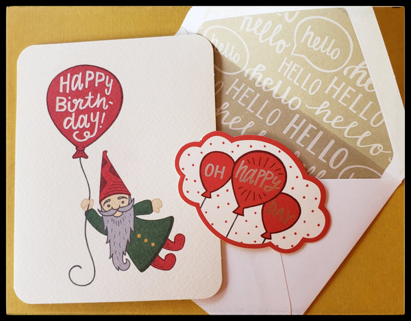 "Gnome holding a balloon that says Happy Birthday while flying away BLANK INSIDE  Matching envelope   Decorative sticker seal   Silver accents   4.5"" x 6"" with envelope ADA The Gilded Page Santa Fe"