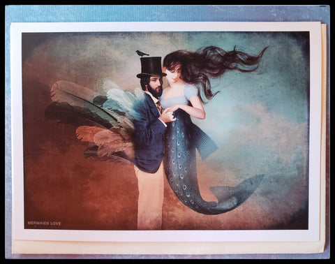 "Mermaids love greeting card. A women as a mermaid holding hands with a human man with feather wings and a top hat. BLANK INSIDE   FSC certified paper card and envelope   5"" x 7.5"" with envelope  ADA The Gilded Page Santa Fe"
