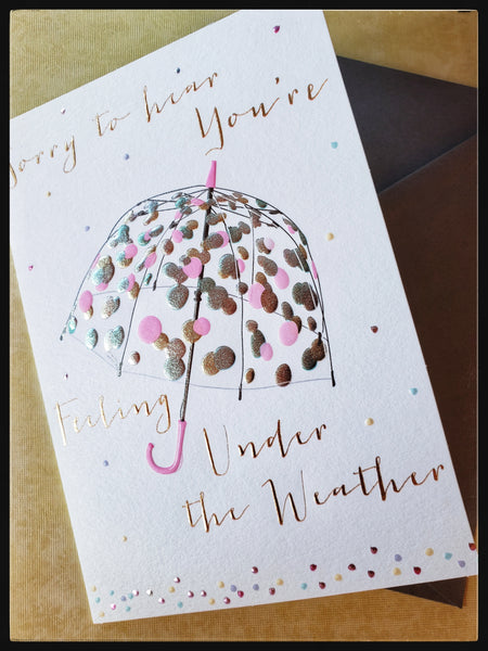 "Message on front Sorry to hear your feeling under the weather with a silver and pink umbrella Inside Message: ""Sending you warm get well wishes""  Embossed details   Metallic accents   Silver envelope   5"" x 7"" with envelope ADA The Gilded Page Santa Fe New Mexico"
