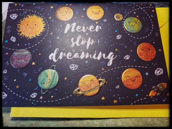 "Front message Never stop dreaming, image is planets Inside Message: ""Graduate, your out of this world! Congratulations""  Glitter accents (glitter does not come off card)   Embossed accents   Yellow envelope   Shiny space planets   5"" x 7"" with envelope ADA The Gilded Page Santa Fe New Mexico"