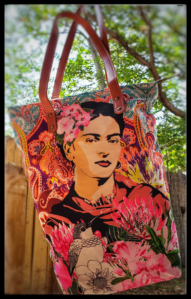 "Frida Kahlo canvas tote Faux leather riveted leather straps   Baby blue inside (inside can be cleaned with soap and water on a towel)  Bright colors  Canvas material with the Frida Kahlo image printed on both sides  Zipper closure   Width 13.5""  Height 17""  Bottom width when open 6""   Straps 13""  ADA The Gilded Page Santa Fe New Mexico"