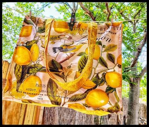 "Lemon Basil design is lush with ripe fruits and green leaves. This tote bag is made of durable 100% cotton, double stitched for strength, and is the perfect size and shape for books, beach towels, or to serve as a reusable shopping bag.   17 x 14"" with 6"" gusset / 43.2 x 35.6 cm with 15.2 cm gusset ADA The Gilded Page Santa Fe New Mexico"