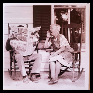 "Elderly couple sitting on a porch, man reading newspaper and women shouting out at me funny anniversary card   Inside Message: ""Happy Anniversary""   6.5"" x 6.5"" with envelope   Light grey envelope ADA The Gilded Page Santa Fe New Mexico"