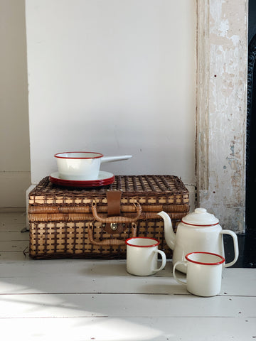 enamel teapot and mugs in cream and red, next to a wicker picnic basket