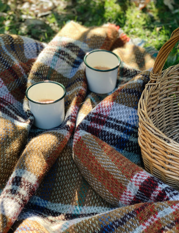 Enamel mugs on a picnic blanket with a wicker picnic basket