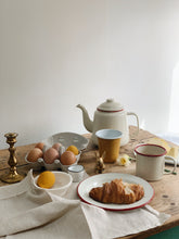 Load image into Gallery viewer, Easter breakfast table, with red and cream enamel teapot, mug and plate. Box of eggs and egg cup, two eggs dyed yellow for easter. Plant dyed napkin, brass bunny and brass candlestick