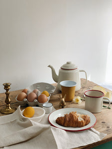 Easter breakfast table, with red and cream enamel teapot, mug and plate. Box of eggs and egg cup, two eggs dyed yellow for easter. Plant dyed napkin, brass bunny and brass candlestick