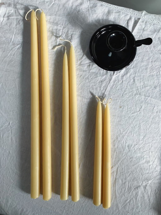 Beeswax tapered dinner candles, displayed in three sizes, next to black enamel candle holder