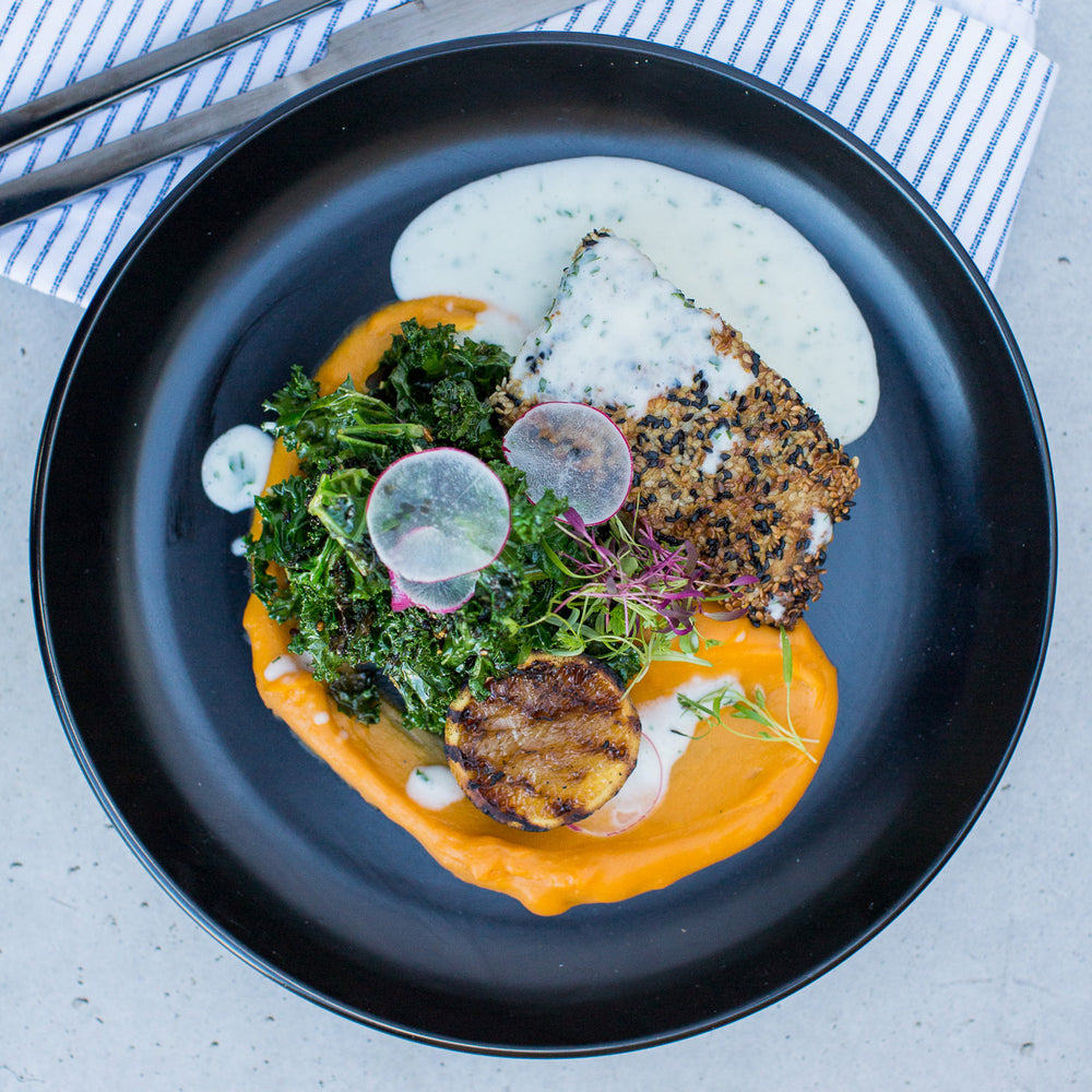 Barramundi, Yam Puree, Greens on a black plate shot from above