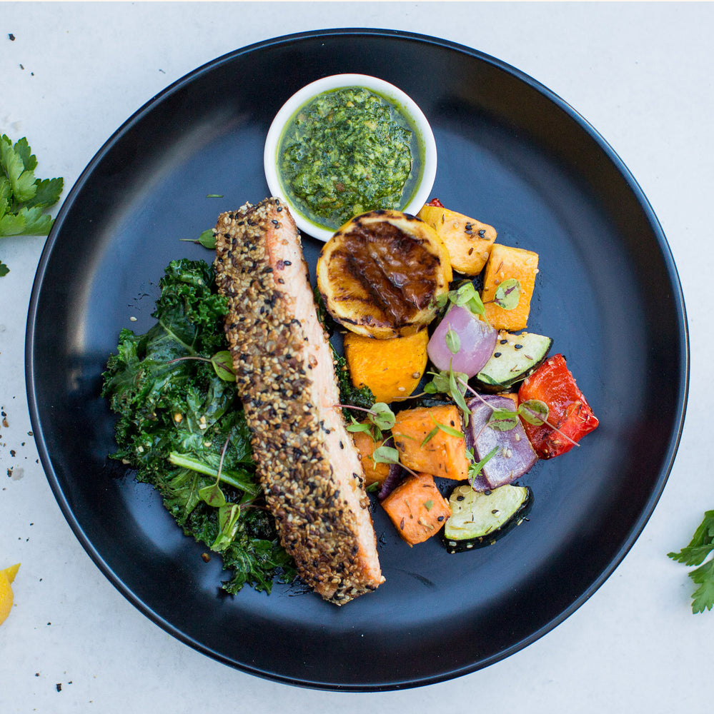 Dukkah Crusted Salmon, Roast Vegetables, Almond & Kale Pesto on a black plate, shot from above
