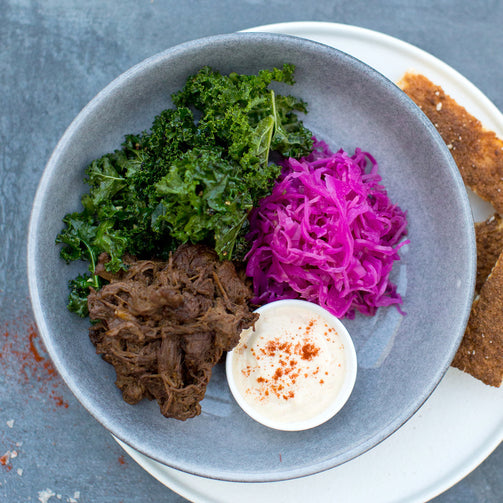 Louisiana Pulled Beef, Braised Red Cabbage, Garlic Kale, White BBQ, in a blue bowl, shot from above