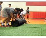 Boys rolling up Premium Turf Roll-Out Mats