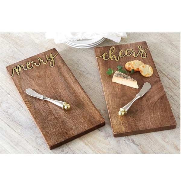 "alt=""Mango wood serving board features hammered gold metal ""cheers"" inset. Arrives with hammered metal spreader with capped gold accent"""