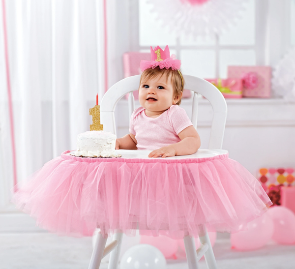 "alt=""Baby girl wearing a pink felt birthday crown with elastic strap, mesh ruffles and a glitter 1 applique with a glitter 1 cake topper on stainless steel post to hold one standard size birthday candle"""