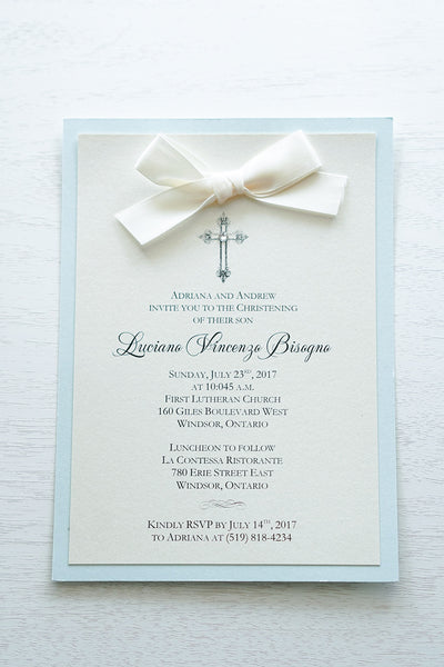 "alt=""Classic Baptism invitation with ivory pearescent shimmer card stock mounted onto a soft blue  pearlescent shimmer cardstock, a rich ivory satin bow and an elegant cross and jewel detail"""